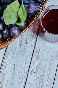 Śliwki ogrodowe w koszu na drewnianym stole ze szklanką soku. wysokiej jakości zdjęcie