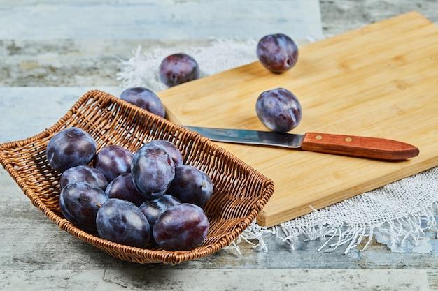 Śliwki ogrodowe w koszu na kamiennym stole z nożem. wysokiej jakości zdjęcie