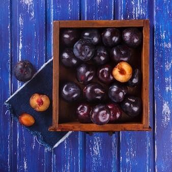 Śliwki w drewnianym pudełku. owoce letnie