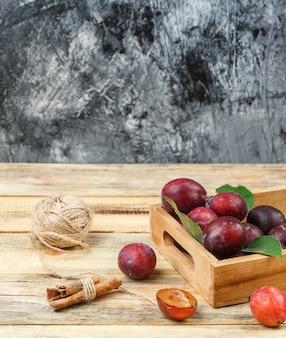 Śliwki z bliska w drewnianej skrzyni z cynamonem i clew na powierzchni drewnianej deski. wolne miejsce w pionie na tekst