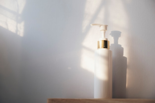 Śliwkowa butelka dezynfekcji rąk na białym tle i światło z okna