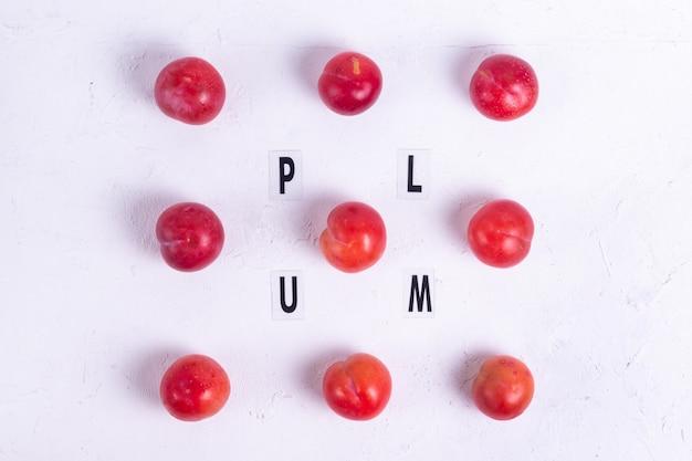 Śliwkowy napis czarnymi literami z dojrzałymi czerwonymi śliwkami