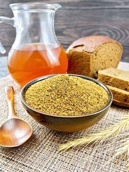 Słód w misce, łyżka, chleb, kwas chlebowy w słoiku na wiklinowej brązowej serwetce na tle drewnianej deski