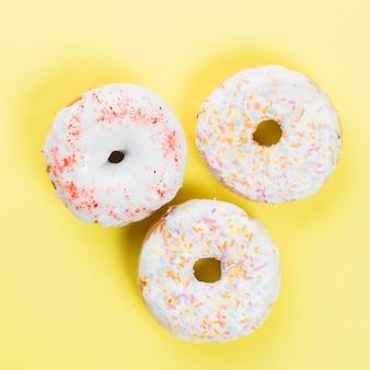 Słodcy donuts glazurujący z kropią na żółtym tle