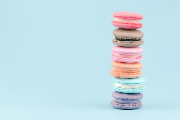 Słodcy francuscy macaroons zasychają z rocznika pastelem barwiącym brzmieniem na błękitnym tle.