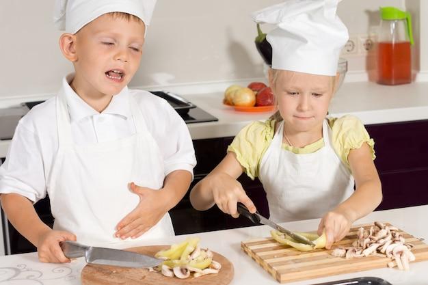 Słodcy mali kucharze kroją składniki pizzy w kuchni