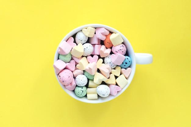 Słodcy marshmallows i cukierki w filiżance na jaskrawym żółtym tle, odgórny widok.