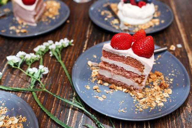 Słodcy torty z letnimi jagodami na drewnianym stole. impreza, słodki stolik. letnia oferta deserów w restauracji.