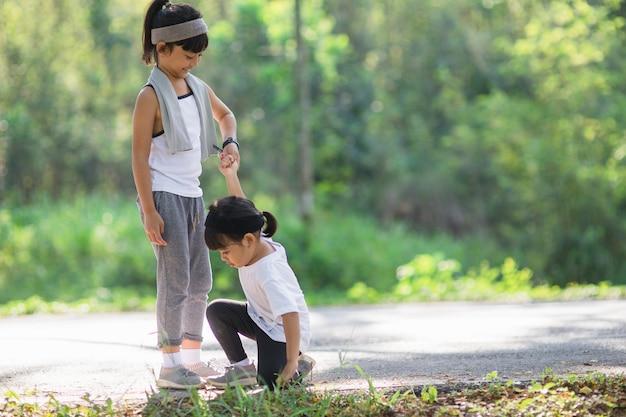 Słodka azjatka podaje rękę, aby pomóc siostrze w wypadku podczas biegania