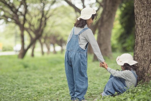 Słodka azjatka podaje rękę, aby pomóc siostrze w wypadku