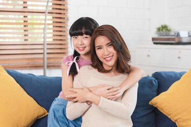 Słodka azjatycka dziewczynka przytula i całuje swoją piękną młodą matkę w policzek, siedząc na kanapie w domu.