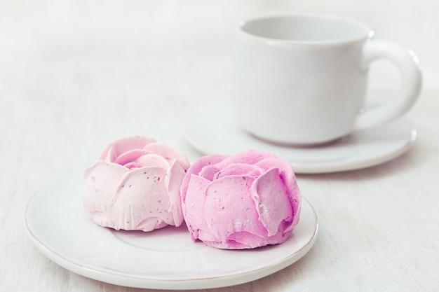Słodka beza z naturalnymi jagodami i filiżanką herbaty