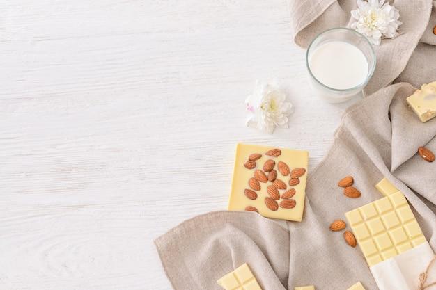 Słodka biała czekolada z migdałami i mlekiem na stole