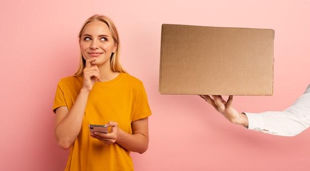 Słodka blondynka z dostępem do internetu otrzymuje pudełko z zamówienia w sklepie internetowym