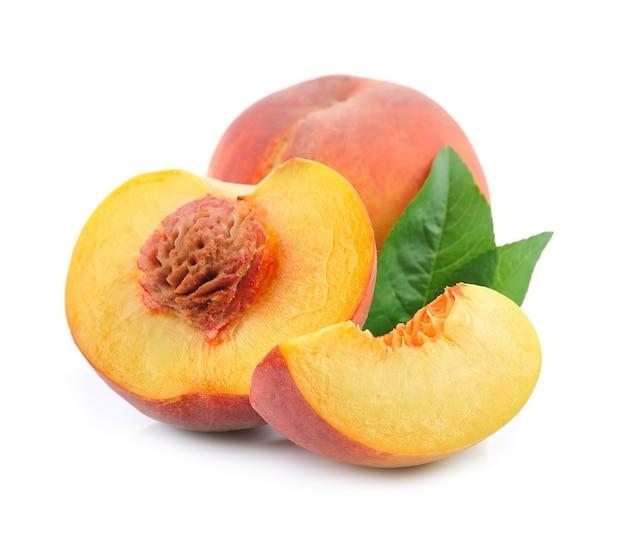 Słodka brzoskwinia z liśćmi na białym tle na białym tle.