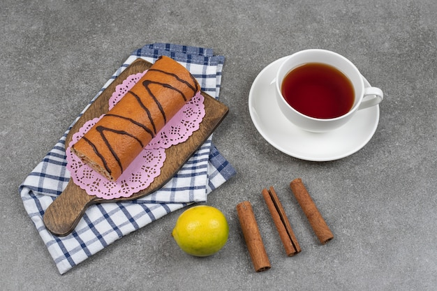 Słodka bułka, filiżanka herbaty i laski cynamonu na marmurowej powierzchni