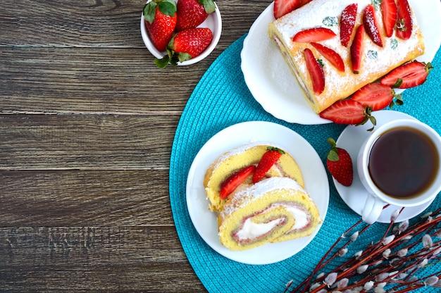 Słodka bułka herbatnikowa z truskawkami i śmietaną, świeżymi jagodami i herbatą. widok z góry