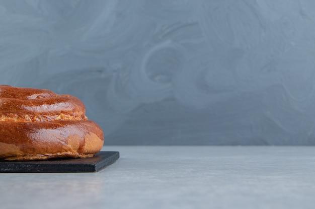 Słodka bułka wirowa na czarnej tablicy.