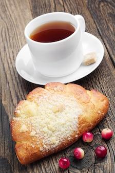 Słodka bułka z filiżanką herbaty i żurawiną na starym drewnianym stole