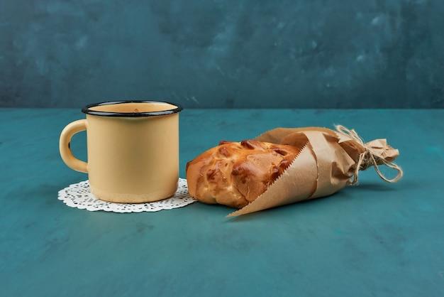 Słodka bułka z filiżanką herbaty ziołowej.