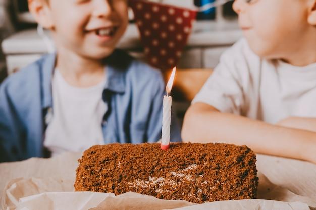 Słodka bułka z nadzieniem czekoladowym i świątecznymi świeczkami i wesołymi dziećmi na neutralnym tle. koncepcja urodziny. ciasto rolkowe ze świeczką, zbliżenie.