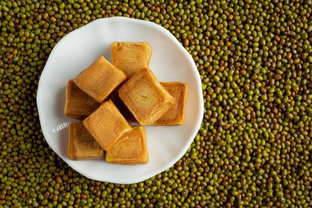 Słodka bułka z pasty fasolowej w białym talerzu ułożona na podłodze pełnej nasion kiełków