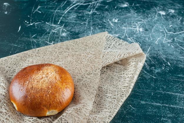 Słodka bułka z ściereczką na marmurowym stole.