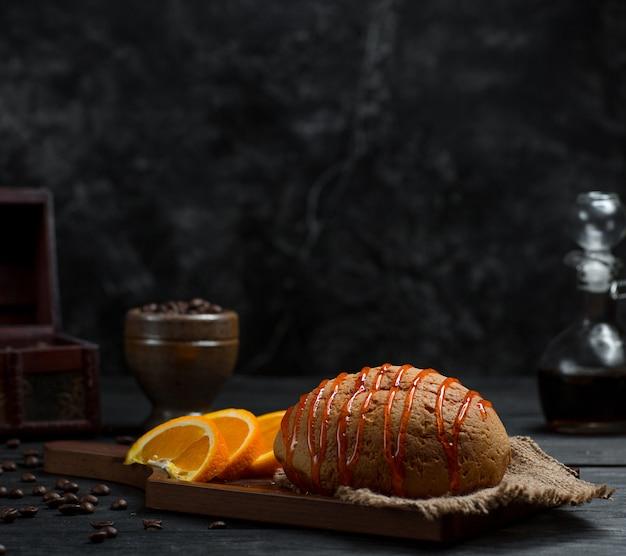 Słodka bułka z syropem wiśniowym i pokrojonymi owocami pomarańczy