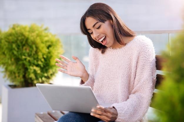 Słodka, bystra, emocjonalna dziewczyna używa swojego laptopa i bezpłatnego wi-fi do dzwonienia do przyjaciółki i rozmów z nią