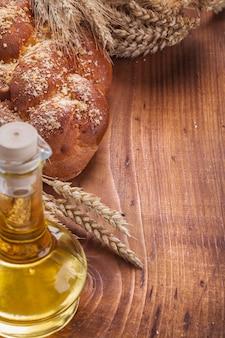 Słodka chlebowa butelka uszy pszenicy z oliwek na vintage drewniane jedzenie i picie koncepcji