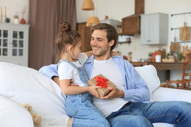Słodka córeczka robi niespodziankę tatusiowi, mała dziewczynka prezentuje pudełko upominkowe ojcu siadającemu na kanapie. dzień ojca.