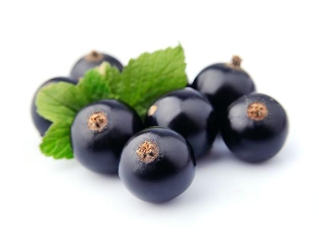 Słodka czarna porzeczka z liśćmi z bliska na białym tle