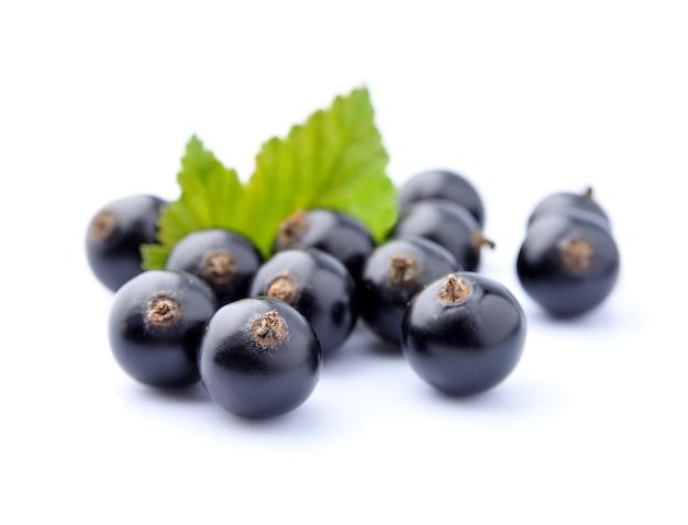 Słodka czarna porzeczka z liśćmi z bliska na białym tle.