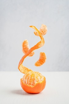 Słodka dojrzała pomarańczowa mandarynka z oderwaną skórką i latającymi lub lewitującymi segmentami na drewnianym stole