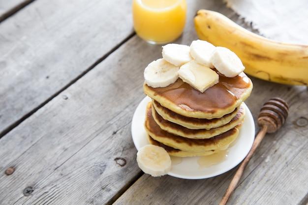 Słodka domowe stos naleśników z masłem, banan i miód na śniadanie
