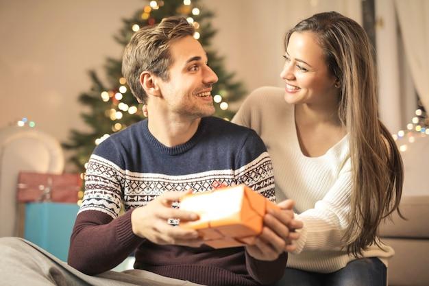 Słodka dziewczyna daje chłopakowi prezent świąteczny