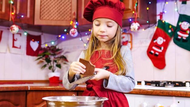 Słodka dziewczyna kucharz ściera czekoladę na tarce do miski. na stole pomarańczowe, różne składniki ciasta. na zapleczu kuchni znajdują się różne ozdoby świąteczne i girlandy