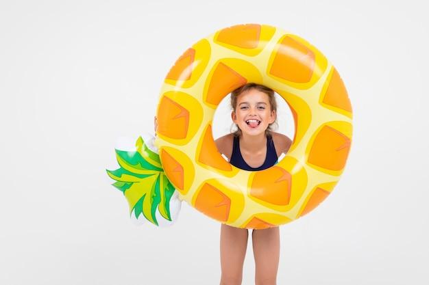 Słodka dziewczyna ma zamiar pływać w morzu z gumowym pierścieniem i materacem na białym tle