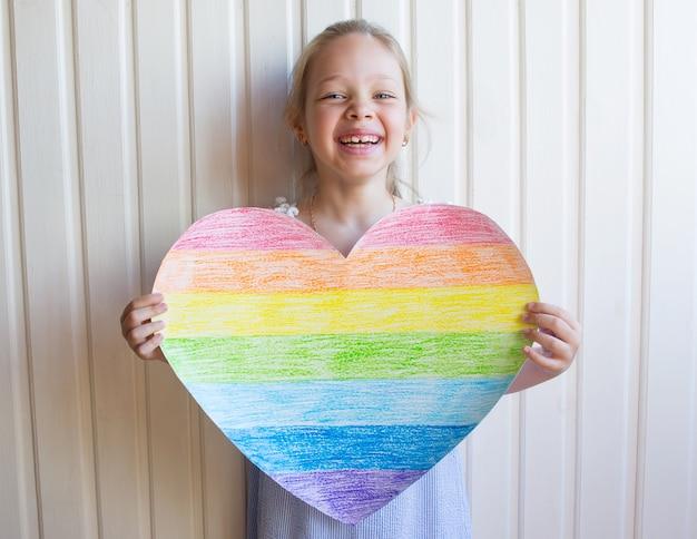 Słodka dziewczyna trzyma w rękach tęczowe serce na białej ścianie