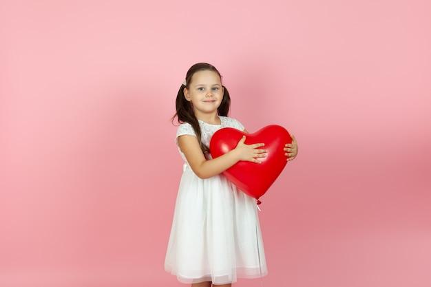 Słodka dziewczyna w białej sukience stoi do połowy bokiem i trzyma czerwony balon w kształcie serca