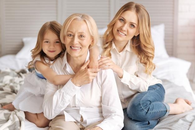 Słodka dziewczynka obejmująca babcię, obejmująca jej dłonie na szyi, podczas gdy matka dziecka opiera dłoń na ramieniu