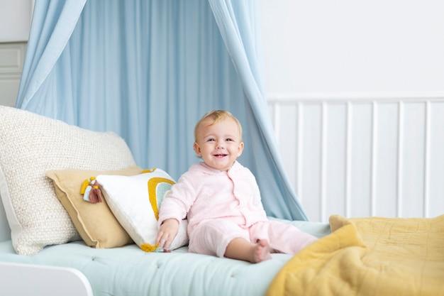 Słodka dziewczynka siedzi na swoim łóżku