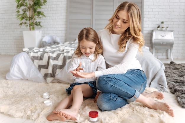Słodka dziewczynka siedzi w objęciach matki i nakłada krem na dłoń.