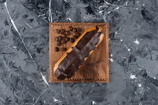 Słodka eklerka z polewą czekoladową umieszczona na marmurowej powierzchni.