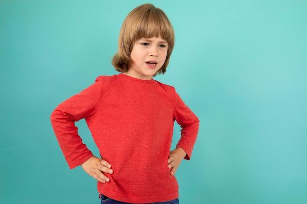 Słodka europejska chłopiec w czerwonym pulowerze pozuje na odosobnionym błękitnym studiu