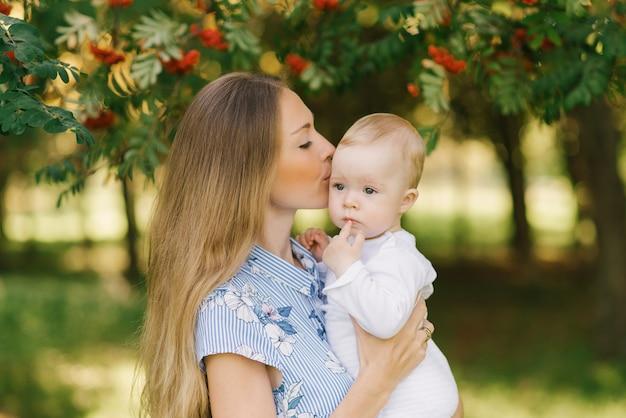 Słodka i delikatna młoda kobieta, europejska matka, trzyma w ramionach swojego małego synka i całuje go w pobliżu gałęzi z czerwoną rowan