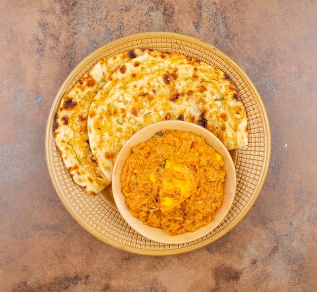 Słodka i pikantna kuchnia indyjska paneer pasanda podana z czosnkiem nan