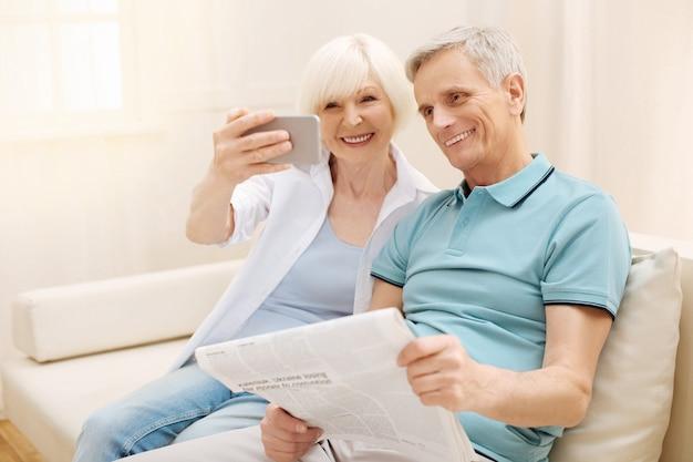 Słodka, inteligentna i elegancka dama używa swojego smartfona i publikuje do zdjęcia, ciesząc się cudownym porankiem ze swoim mężczyzną