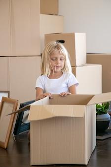 Słodka, jasnowłosa dziewczynka rozpakowuje rzeczy w nowym mieszkaniu, siedzi na podłodze obok otwartego pudełka z kreskówkami i zagląda do środka