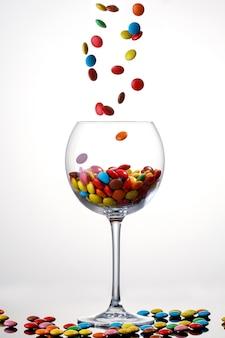 Słodka kolorowa cukierek pokrywająca czekolada spada wewnątrz szkło na białym tle.